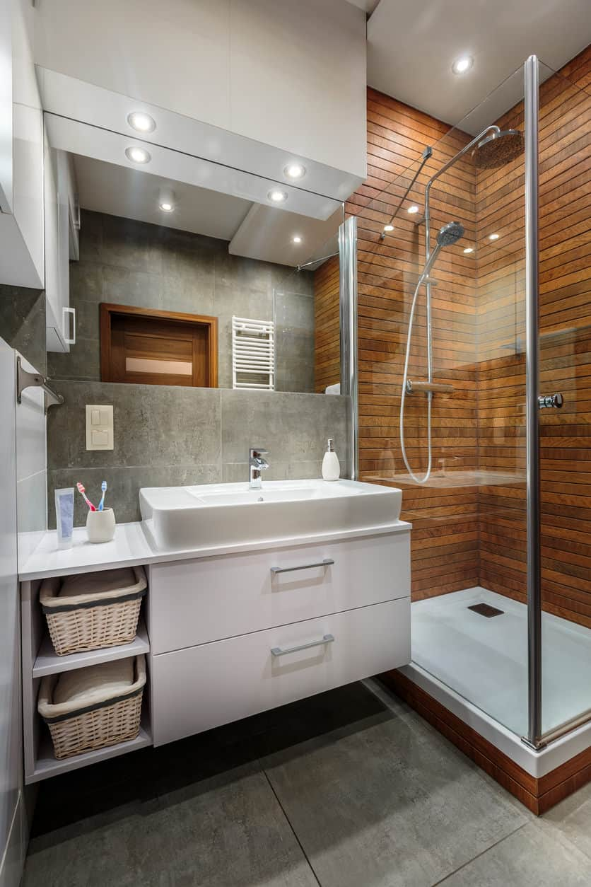 Another fabulous small primary bathroom with wood wall in shower (very interesting) and small floating modern white vanity. I like the gray tile wall above white vanity along with recessed lights thoughout.