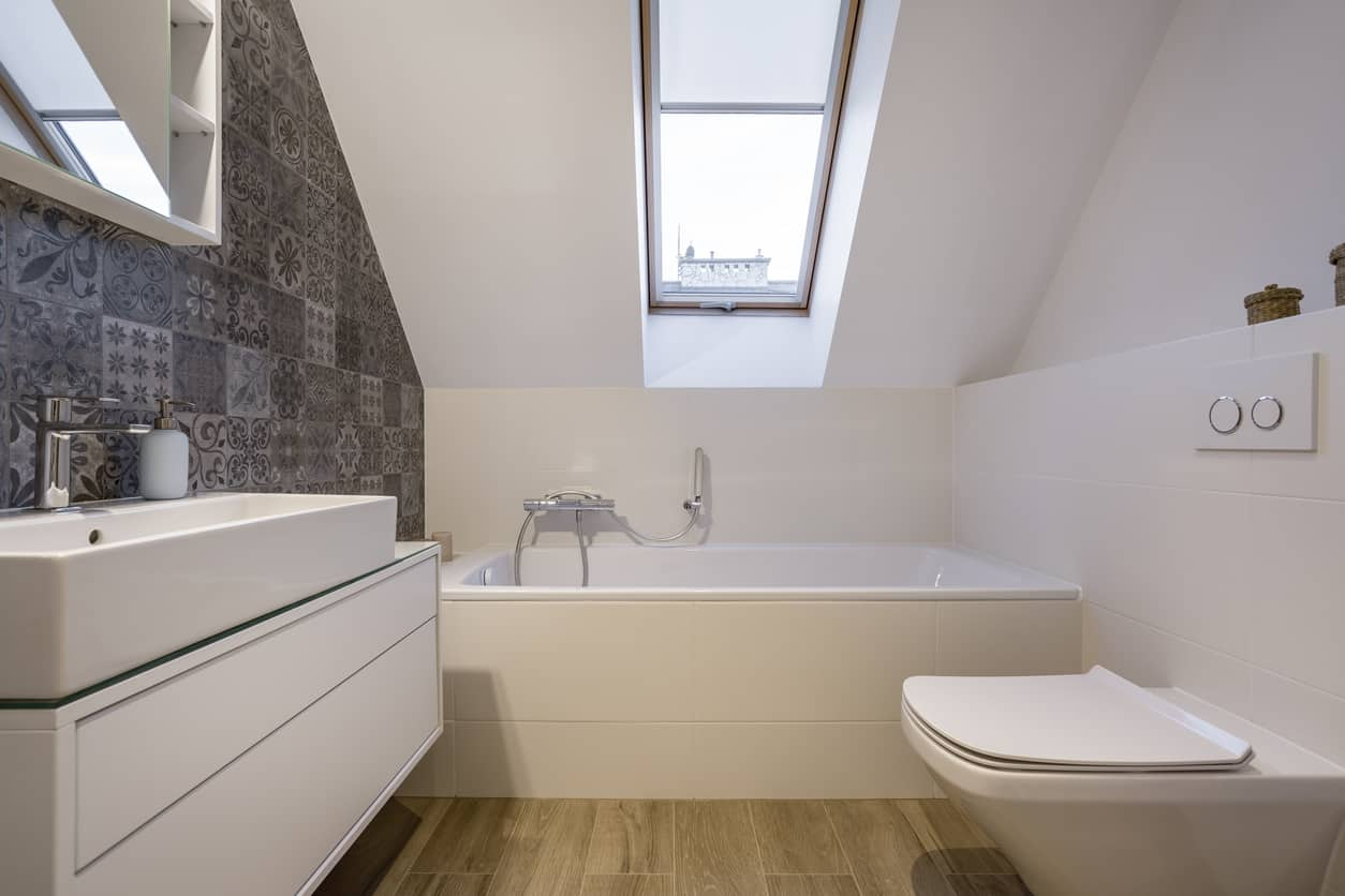 Small primary bathroom in the attic with skylight, small tub and long trough-like modern sink.