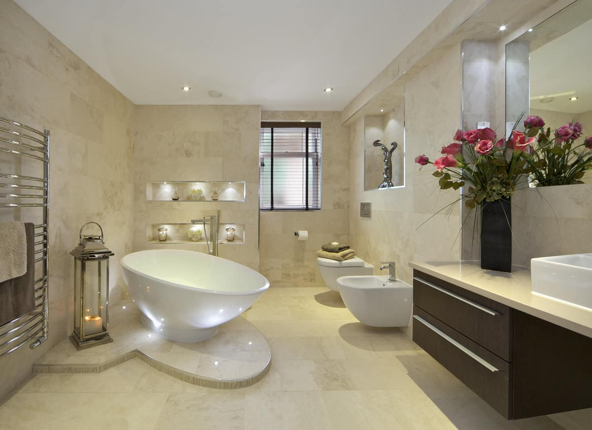 Elegant primary bathroom with beige walls and floors, a freestanding tub, floating toilets, and floating vanity.