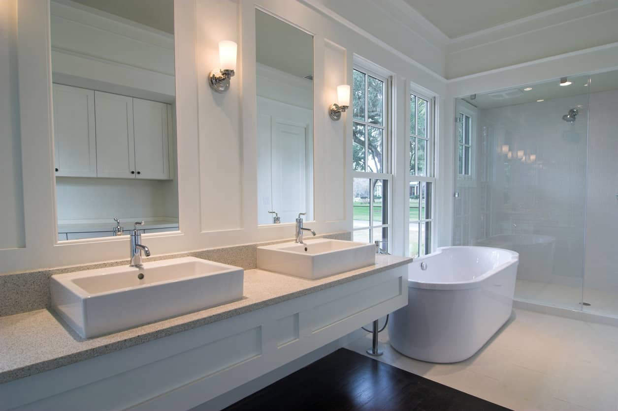 Long white primary bathroom with both freestanding white tub and large walk-in shower. Includes long vanity with two modern style sinks. Tall window next to tub. Also, check out the floor - part of it is tile and the other part is dark wood.