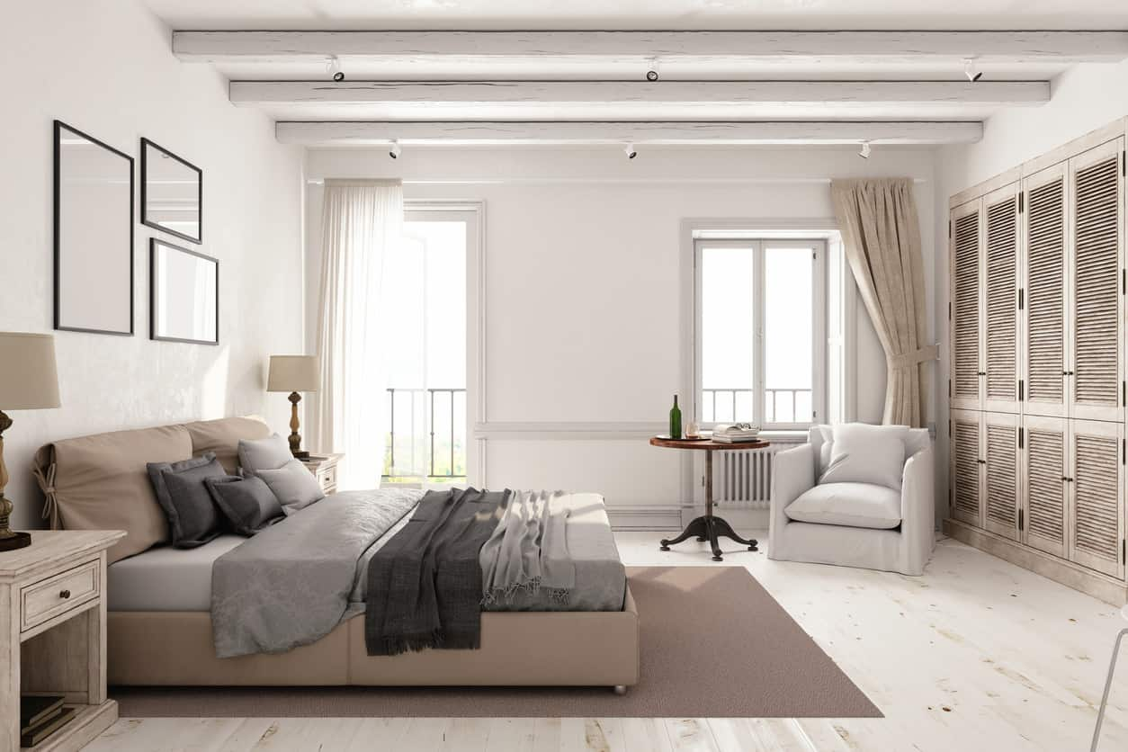What an absolutely gorgeous Scandinavian primary bedroom with simple platform bed, distressed white/light brown closet doors, birch wood flooring, off-shite armchair and distressed nightstands. Two large windows emit plenty of natural light. Notice the white-washed wood ceiling as well... lots of white, but all the natural wood makes it look amazing.