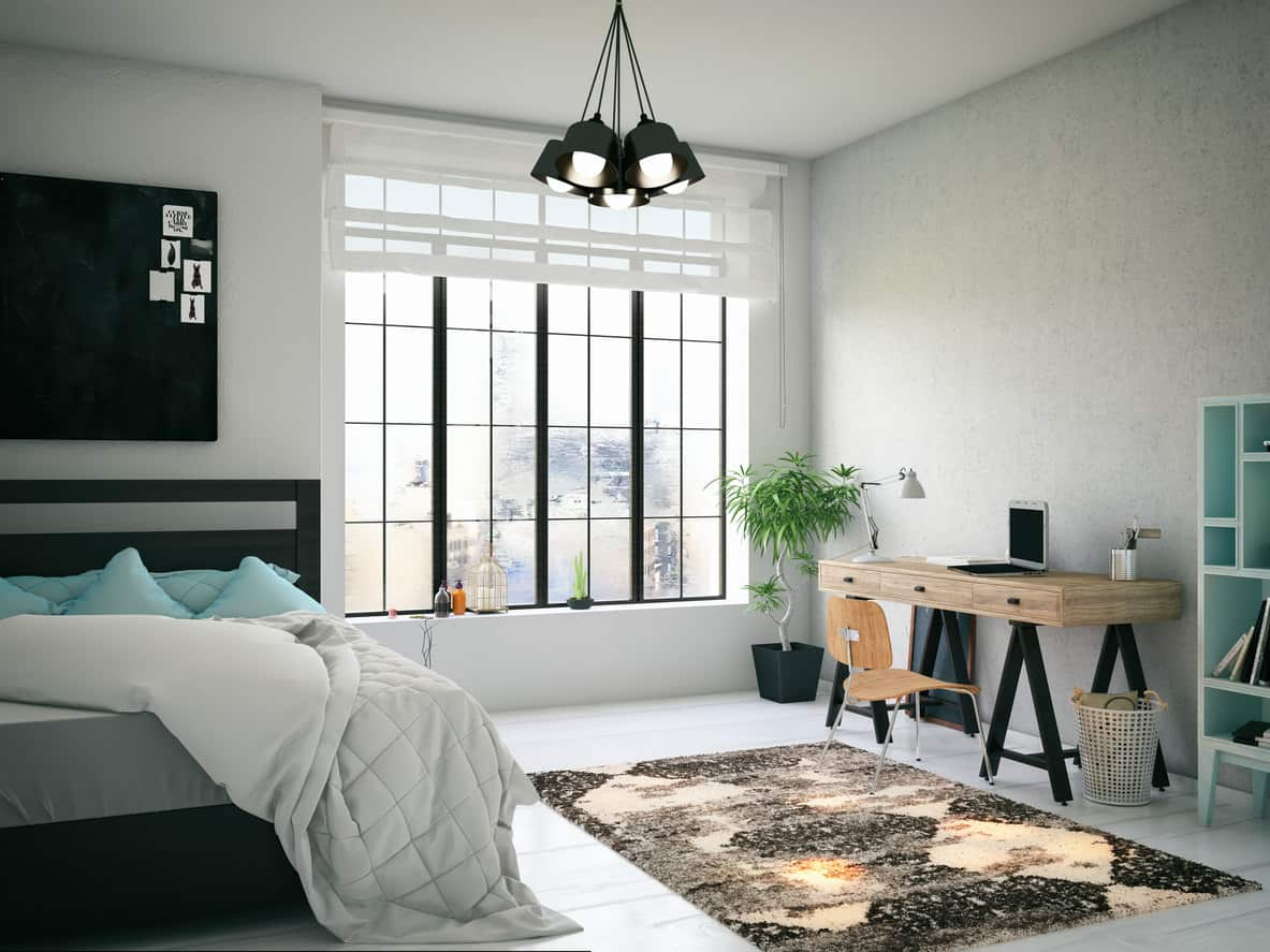 Spacious white and light gray loft primary bedroom with large black-framed window, platform bed and cool modern desk all on white wood flooring.