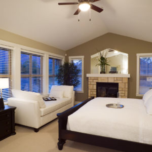 Gorgeous primary bedroom with cathedral ceiling, divan, ceiling fan, lots of windows and beautiful bed.