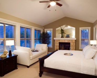 Gorgeous master bedroom with cathedral ceiling, divan, ceiling fan, lots of windows and beautiful bed.