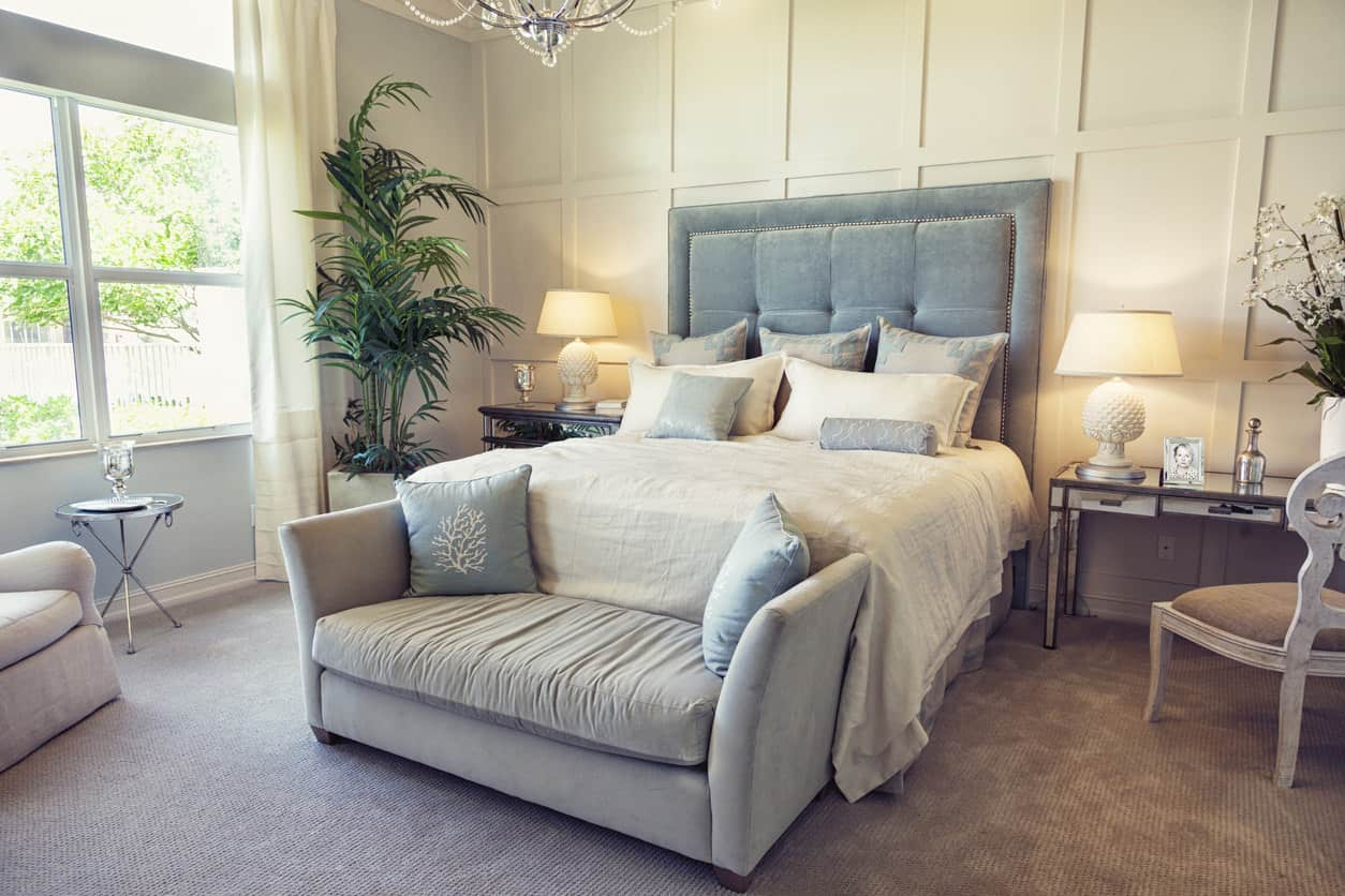 Glam and comfort make up this nicely textured bedroom decor. The paneled ceiling, suide tufted headboard, sitting furniture, curtains and chandelier give this primary bedroom a unique decor style all its own.