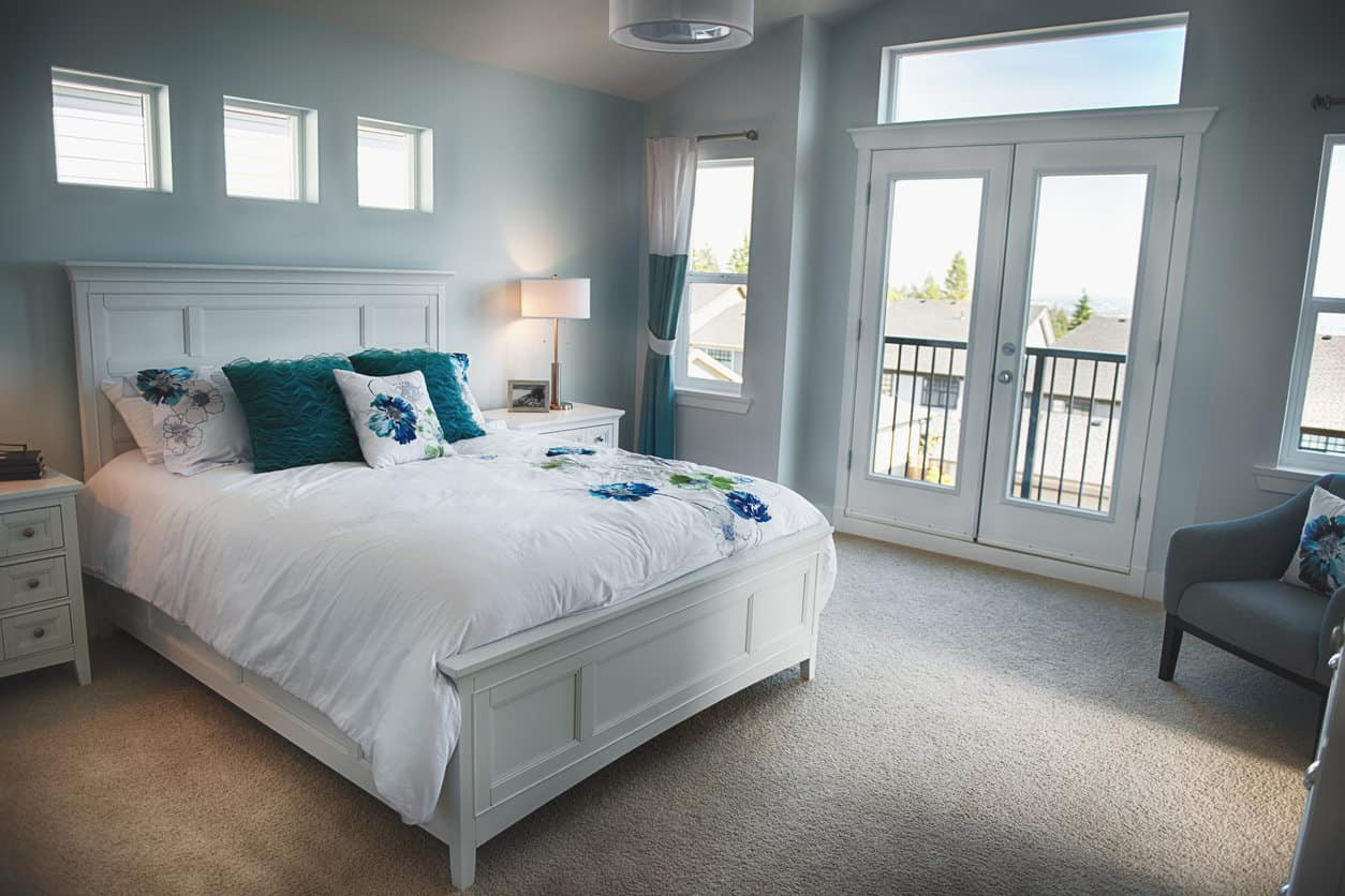 Blue beach style primary with a fabulous white bed and balcony. It's in a suburban home which works, but imagine this overlooking the beach... now that would be perfection.