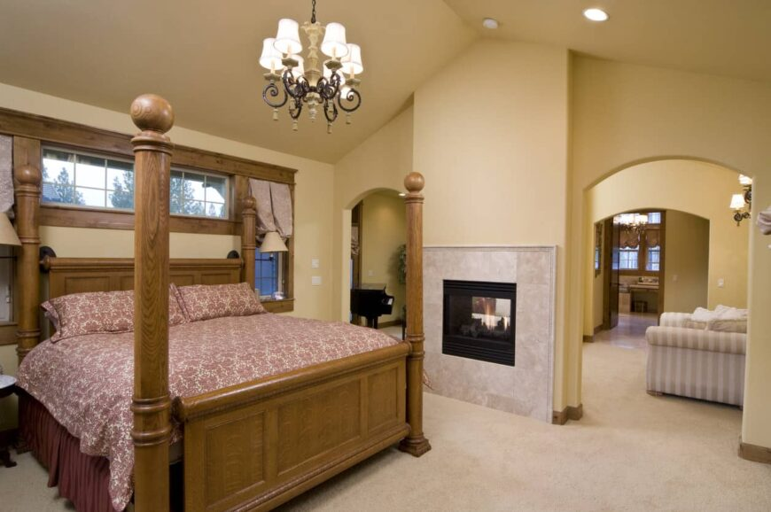 Mediterranean primary bedroom with carpet floors and beige walls. The room offers a classy bed and a fireplace, lighted by a stunning chandelier.
