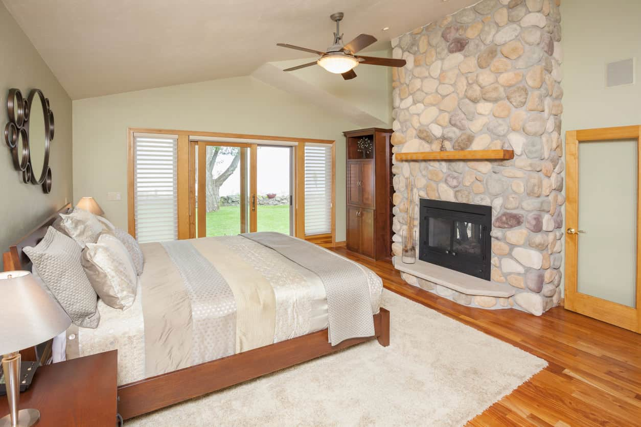 Plain decor with the river rock fireplace being the centerpiece is what this farmhouse style primary bedroom is all about.