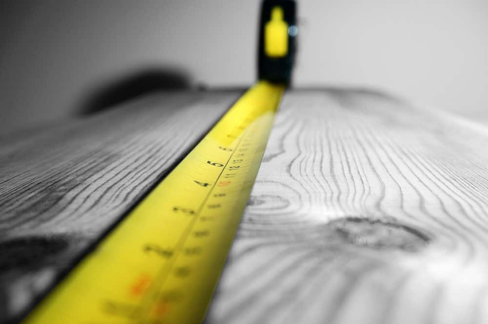 Measuring tape pulled out to measure a wooden slab.