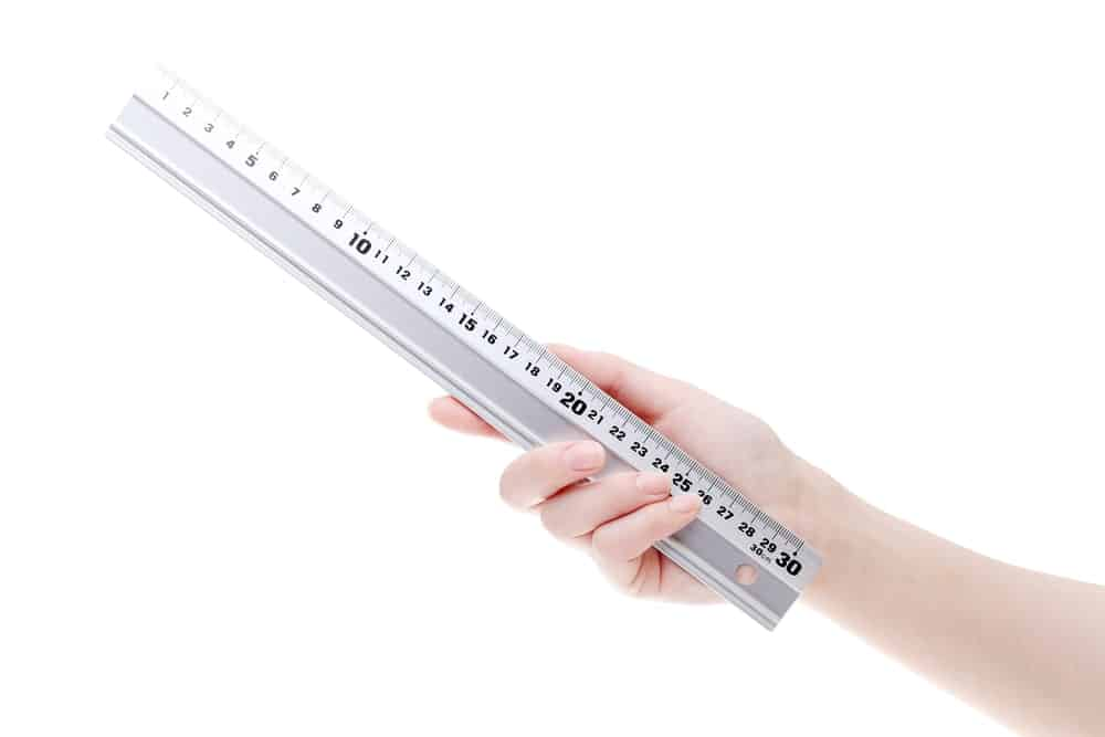 Hand holding a metal ruler on white background.