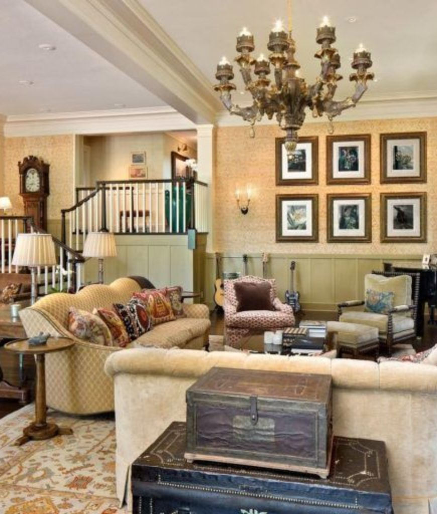 The formal living room boasts elegant furniture set along with the chandelier. The room also features a fireplace.