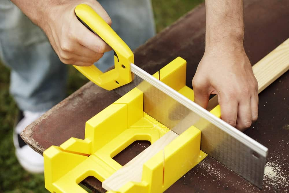 Cutting a thin strip of wood using a small hand saw and a miter box on wooden table.