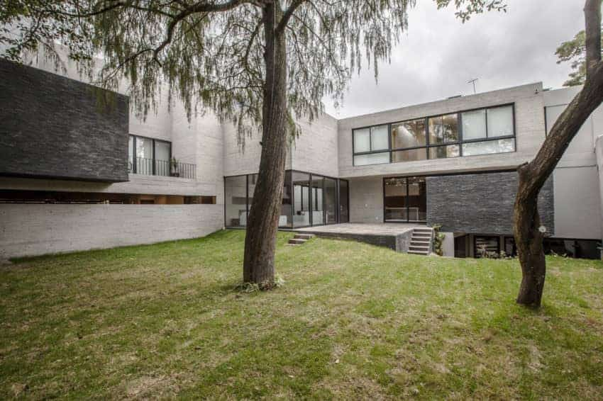 Large modern concrete house with gray finishes along with a sprawling lawn area.