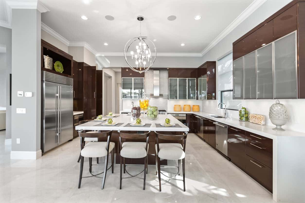 All White Modern Kitchen Large U-shaped modern kitchen with square island that accommodates 5  stools. Notices the
