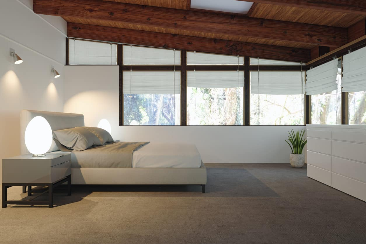 Modern loft primary bedroom with wooden shed ceiling, platform bed, white walls and beige furniture.