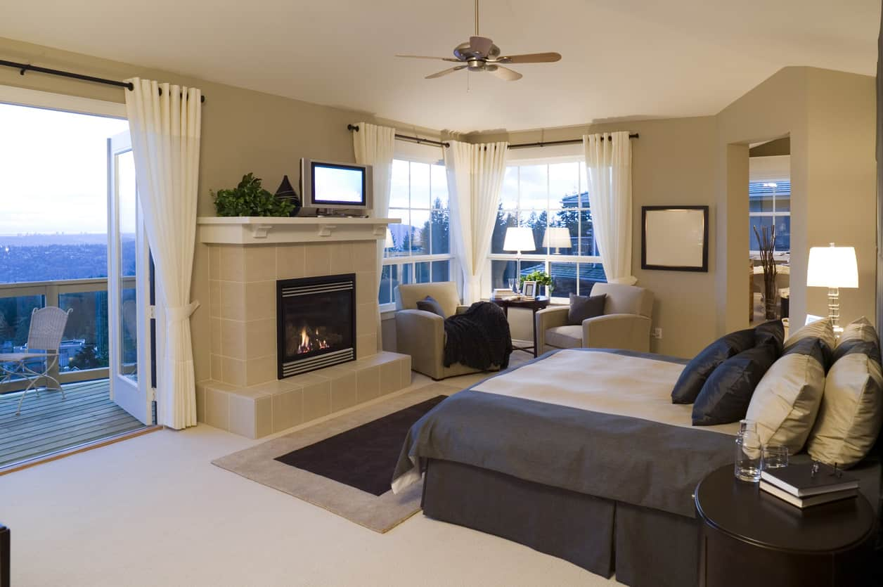 A beautiful contemporary primary bedroom with fireplace, balcony and lovely reading nook corner.