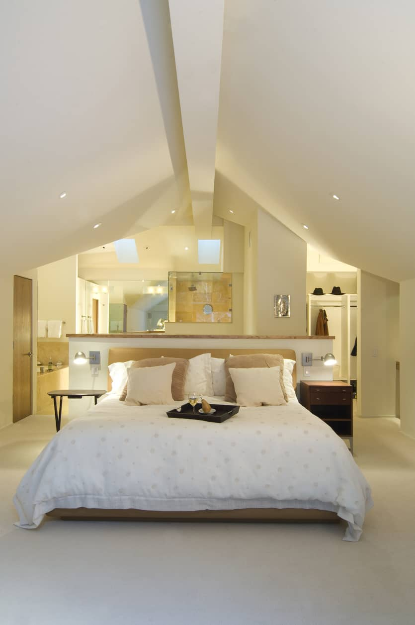 White primary bedroom with cathedral vaulted white ceiling. Bedroom area opens up on both sides to stylish en suite. Very minimalist design throughout.