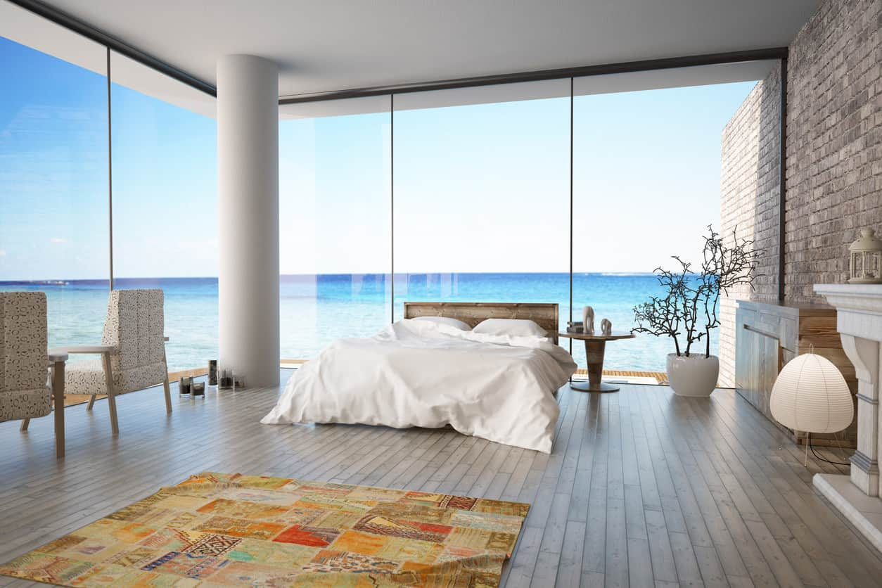 Ocean view modern primary bedroom with brick wall, wood floor, colorful area rug, pure white ceiling and incredible floor-to-ceiling windows.