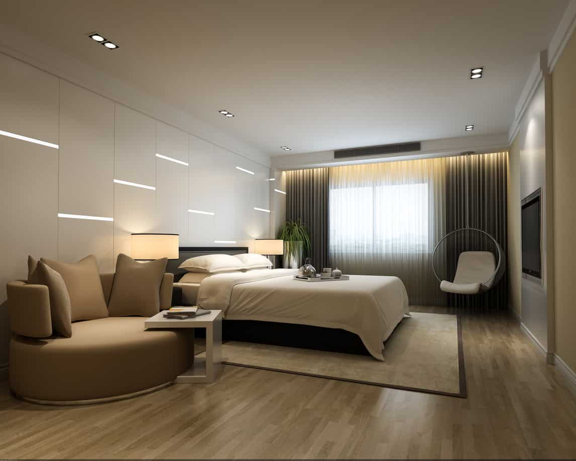Interesting bedroom design with round sofa, built-in LED wall lighting and recessed lighting on light hardwood floor.