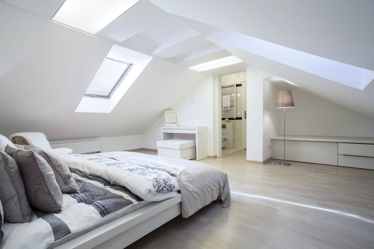 Attic mater bedroom with white angled walls/ceiling, skylight, large platform bed and en suite.