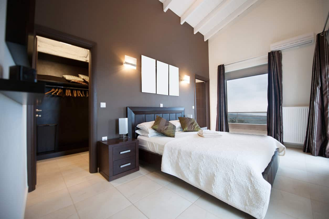 Modern primary bedroom with a walk-in closet, dark accent wall, tile flooring and cathedral ceiling