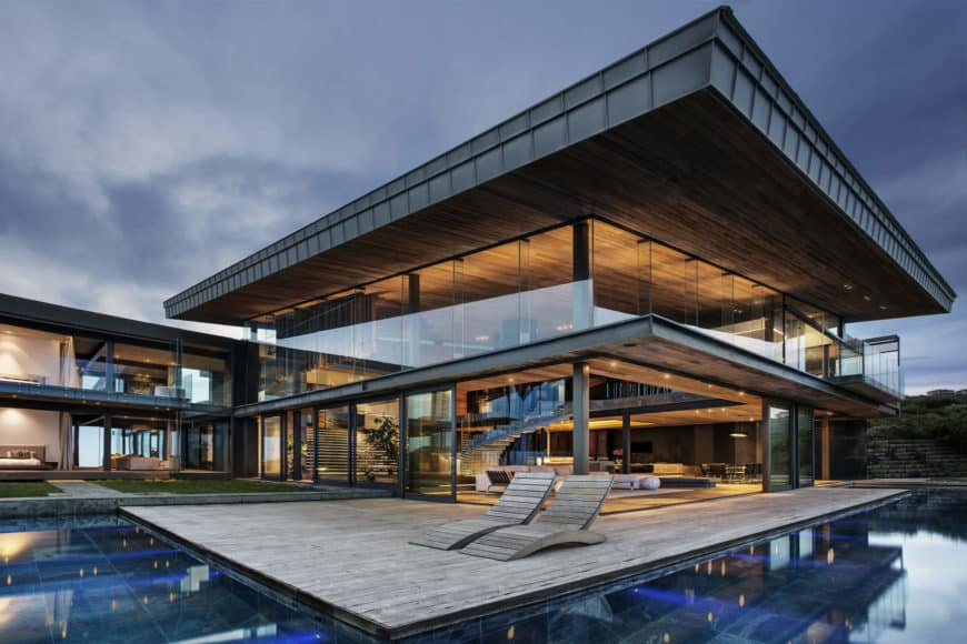 Huge modern home with a gray exterior. It also boasts a gorgeous outdoor area with a swimming pool and a deck.