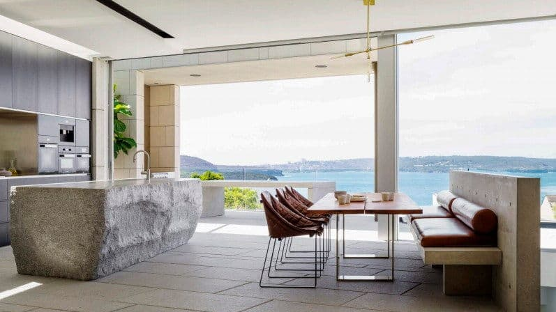 A dining nook across the stone island bar showcasing metal dining table and round back chairs along with a built-in seating fitted with red leather cushions. It has panoramic windows overlooking a stunning ocean view.