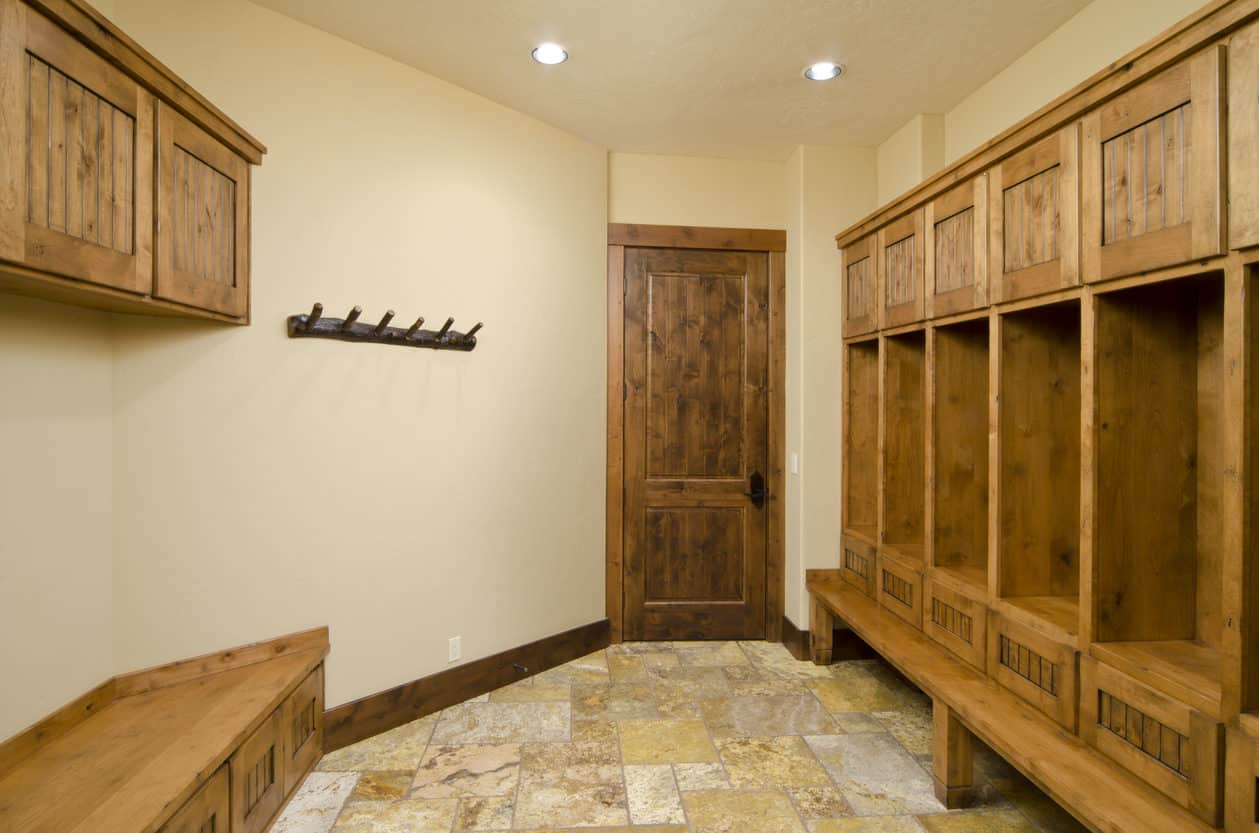 This mudroom sports a wooden theme where everything is made of wood including the bench, lockers, and shelves. The lockers are separated with a wooden slab in between, which makes it easier to allot separate spaces to different household members.