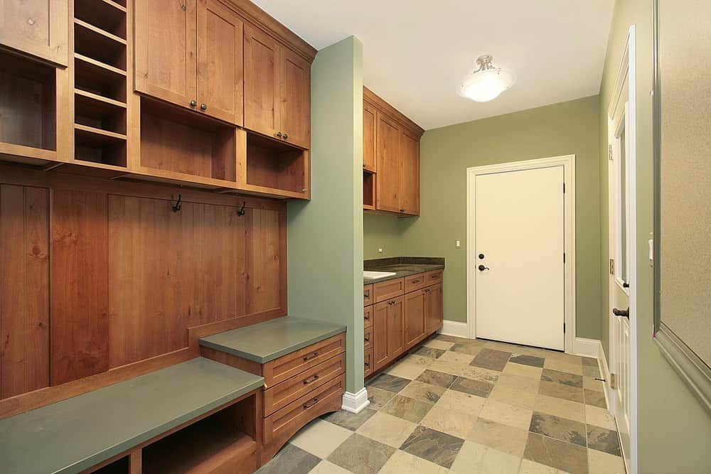 While most mudrooms are white in color, this one uses natural wood, green walls, and square tiles. It is almost like a full-fledged room with a sink, a door, and several storage spaces which is quite handy for someone who has a lot of storage items.