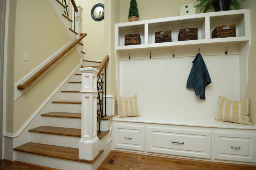 Mudroom area and coat rack with bench in foyer of home at bottom of stairs