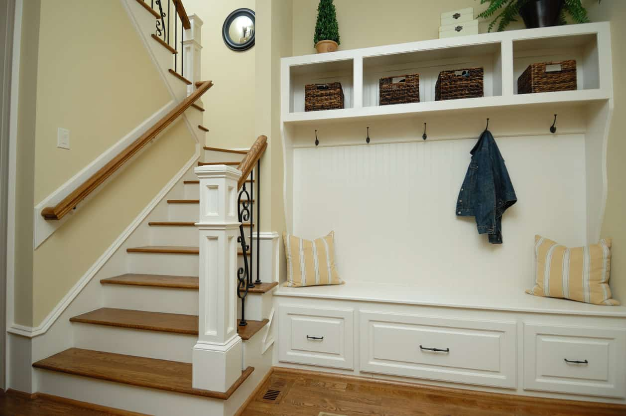 Mudroom Area And Coat Rack With Bench In Foyer Of Home At Bottom Stairs