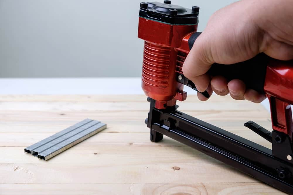 Using a nailer on wooden desk.