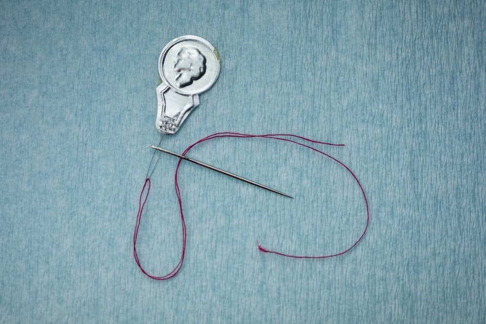 Needle threader with violet thread and needle on blue background.