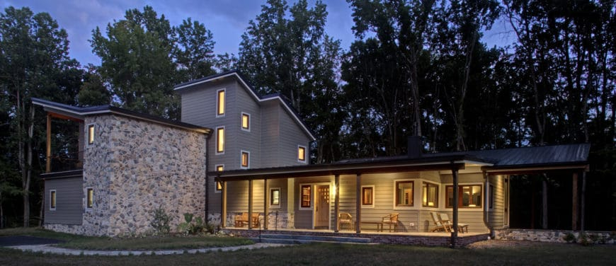 This beautiful gray home is surrounded by mature tall trees and has a lovely garden area.