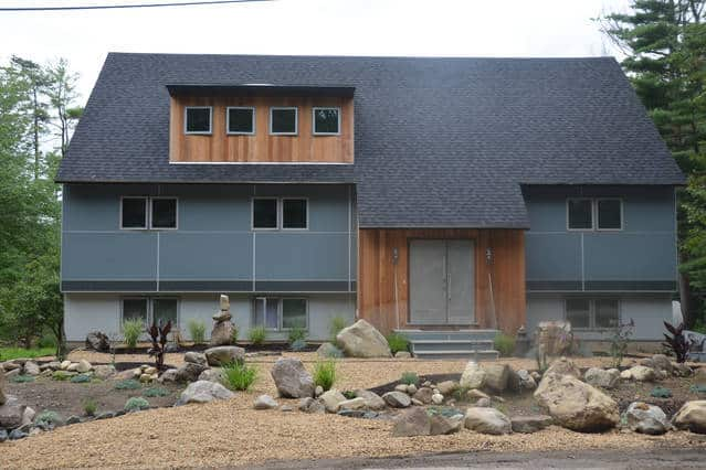 A contemporary loft home with a gray exterior and a gorgeous front yard.