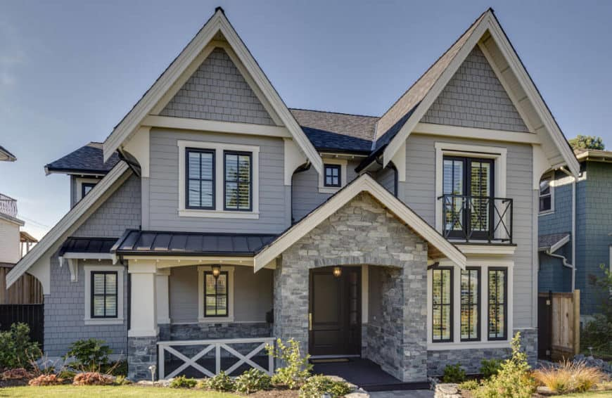 A custom home with a gray exterior and a nice front garden.