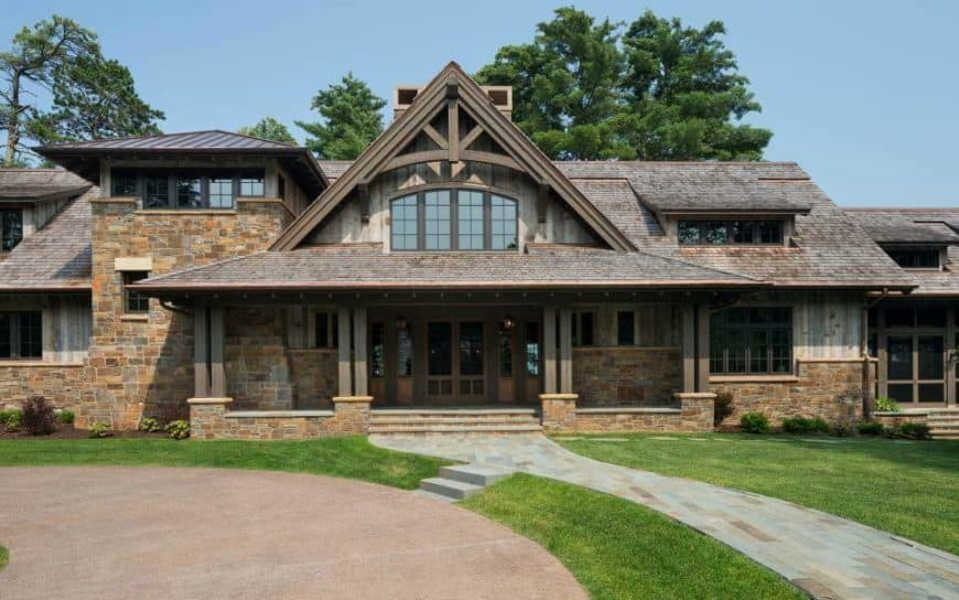 Large stone-exterior house with a nice front yard, walkway and driveway.