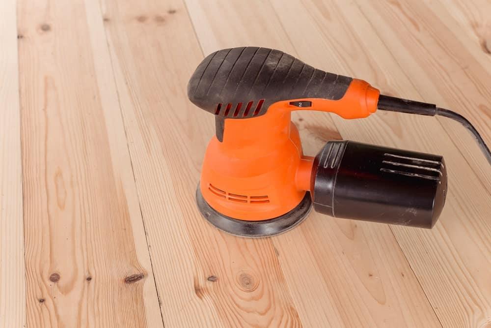 Orange orbital sander on hardwood flooring.