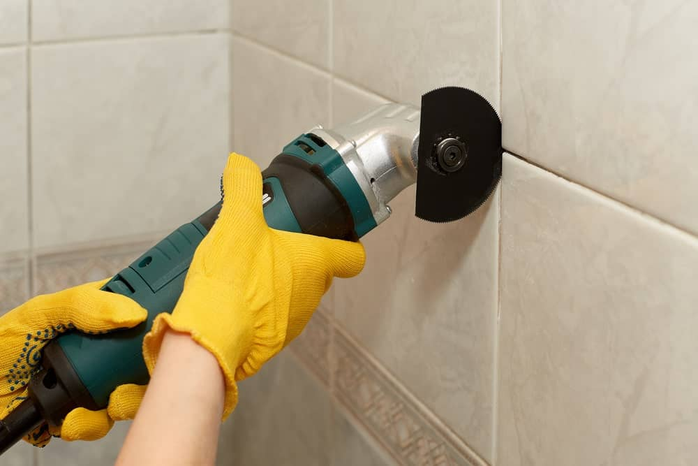 Removing the grout using an oscillating multi-tool.
