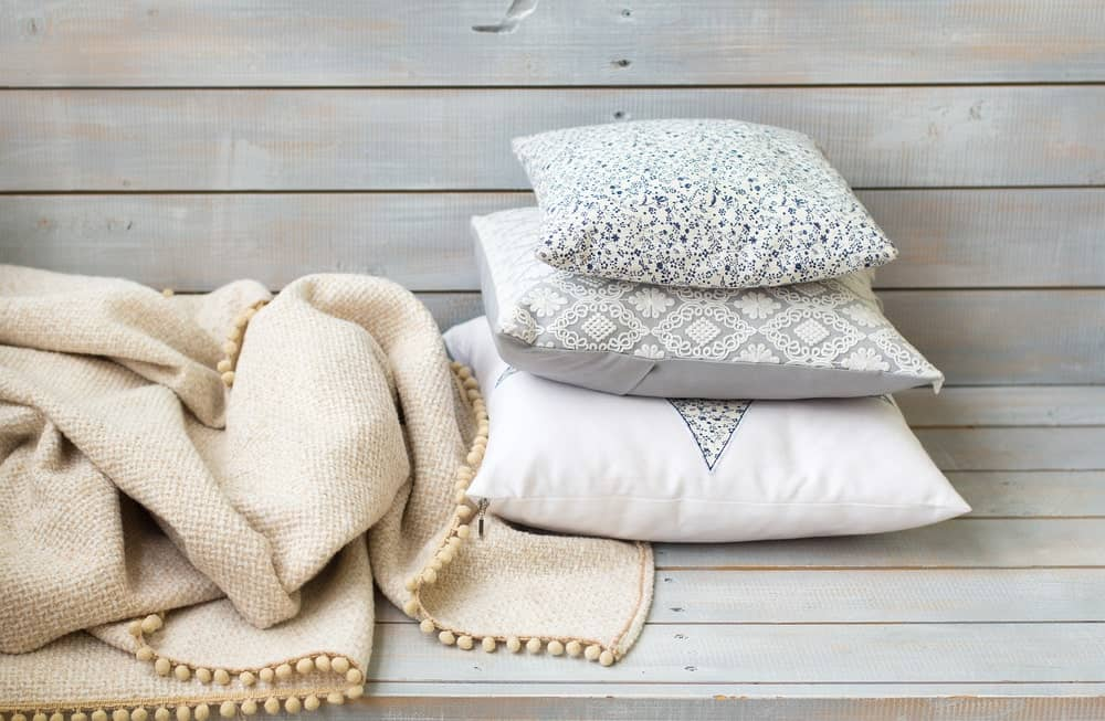 Blanket and pillows on wooden background.