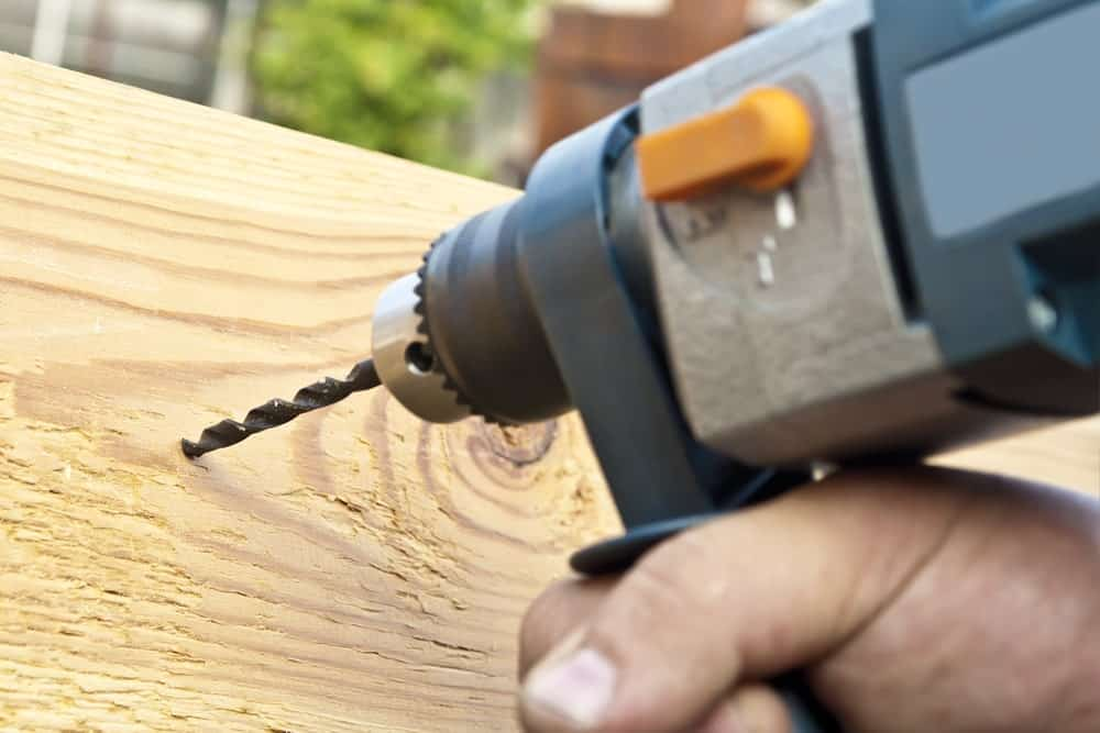 Power drill used to drill a hole through the wood.
