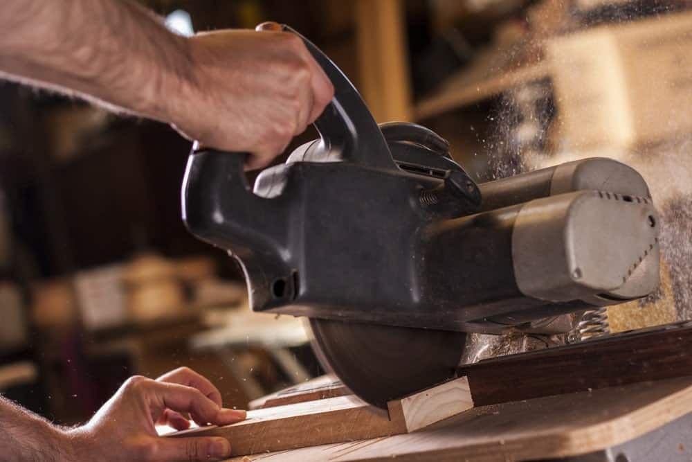 Close up of a power miter saw used to cut a piece of wood in a workshop.