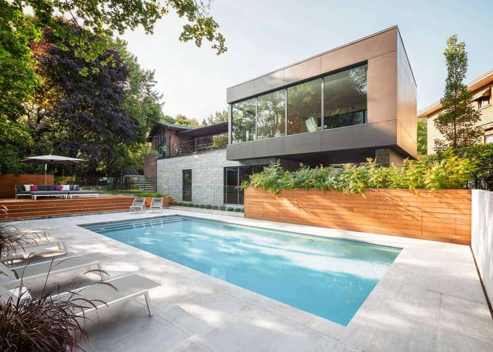 A modern gray-exterior house featuring a cozy outdoor area with a swimming pool and multiple lounges.