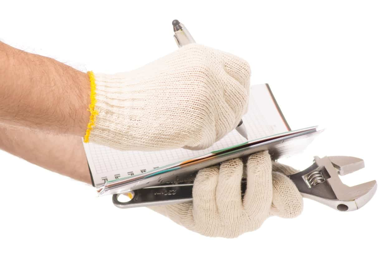 A pair of hands in protective glvoes while writing on a notebook and holding a tool.