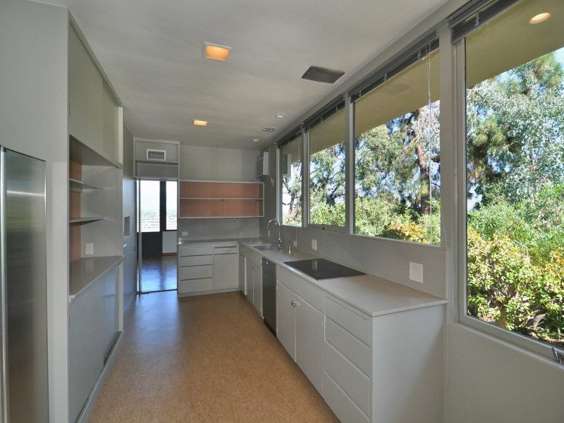 The kitchen features white cabinetry, walls and glass windows overlooking the mature trees outside.