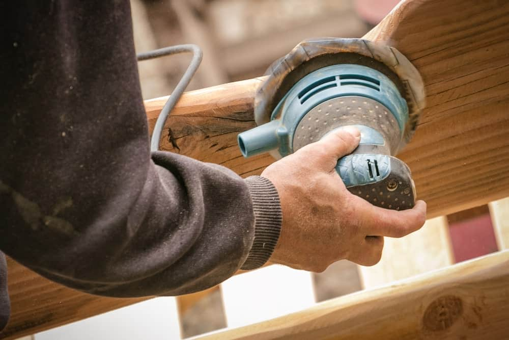 Hand seen polishing the back of a wood using a random orbital sander.