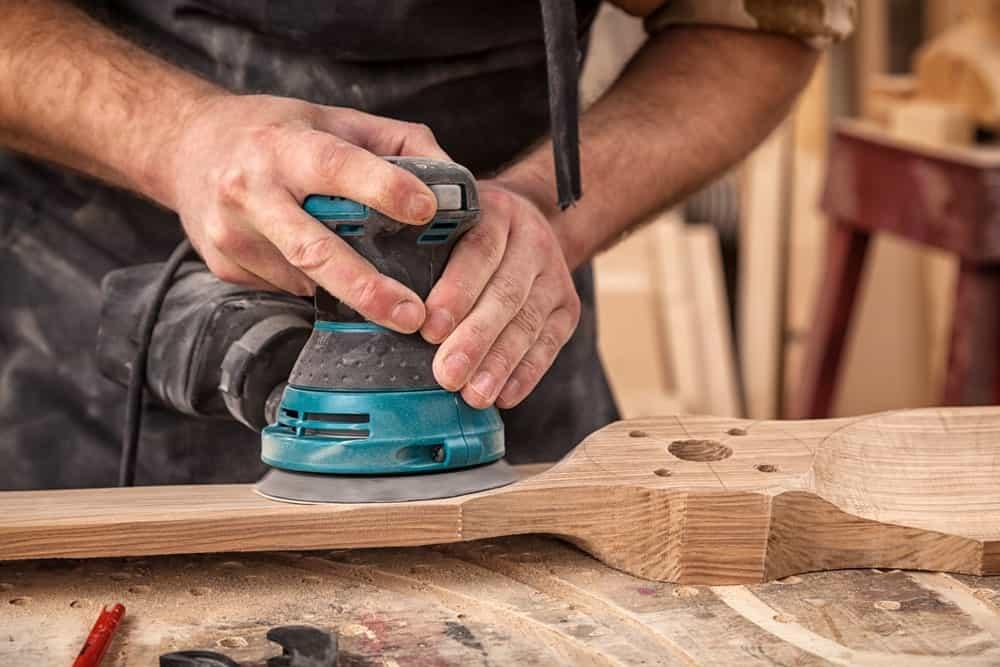 Person using a random orbital sander to polish a piece of wood.