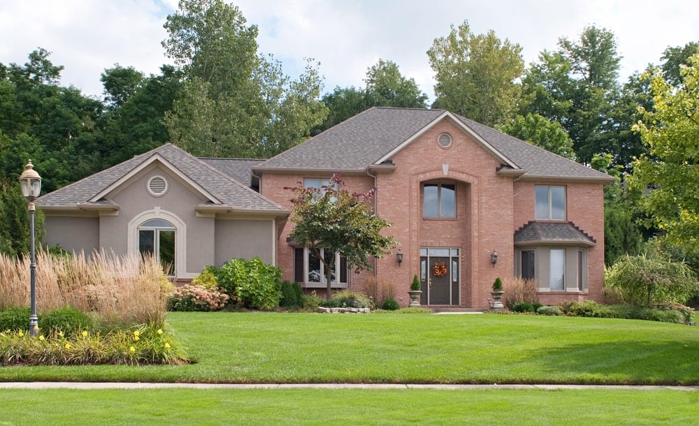 Red brick tan stucco house exterior with well-trimmed lawn.