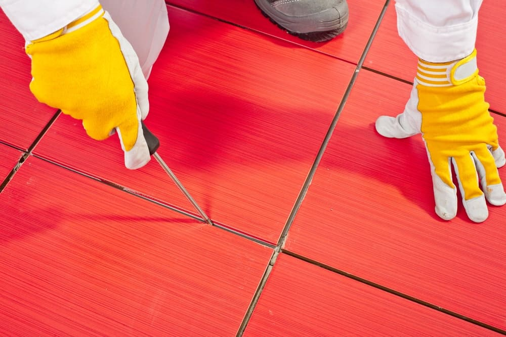 A pair of hands in rubber gloves with one holding a screwdriver pointed along the grout lines of red square flooring tiles.