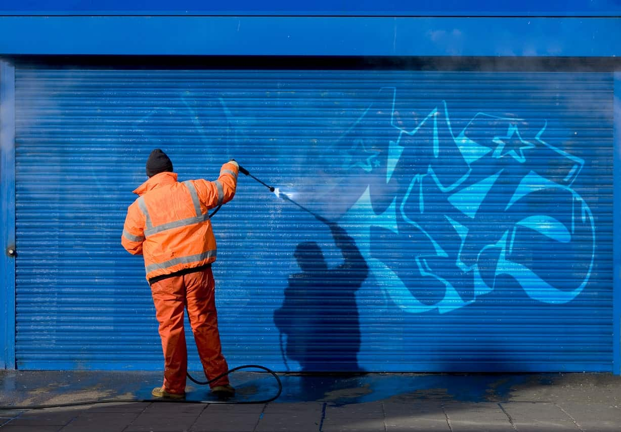 Man using a pressure washer to remove the painting from the wall.